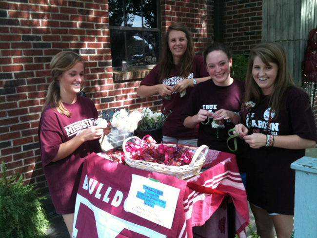 Members of MSU's Student Chapter of the American Institute of Floral Designers offer football game attendees corsages in the school colors of maroon and white, celebrating and continuing a football tradition.
